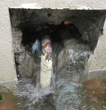 Hole in a wall with water gushing through from a burst pipe